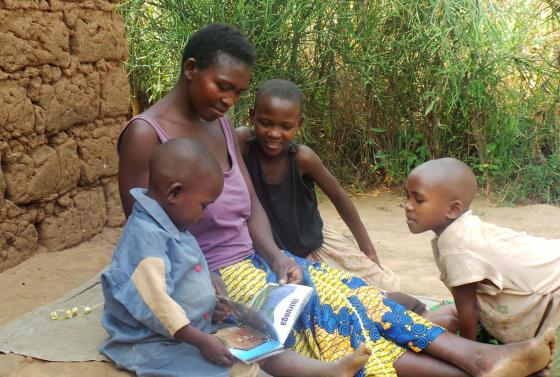 A Rwandan mother reads to her three young children as part of the Sugira Muryango implementation program.