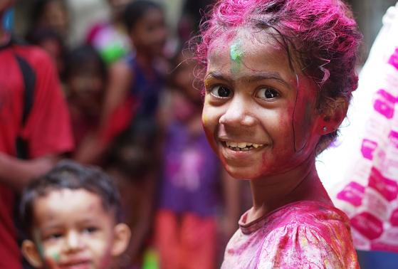 A young girl covered in pink paint celebrates in Mumbai, India.